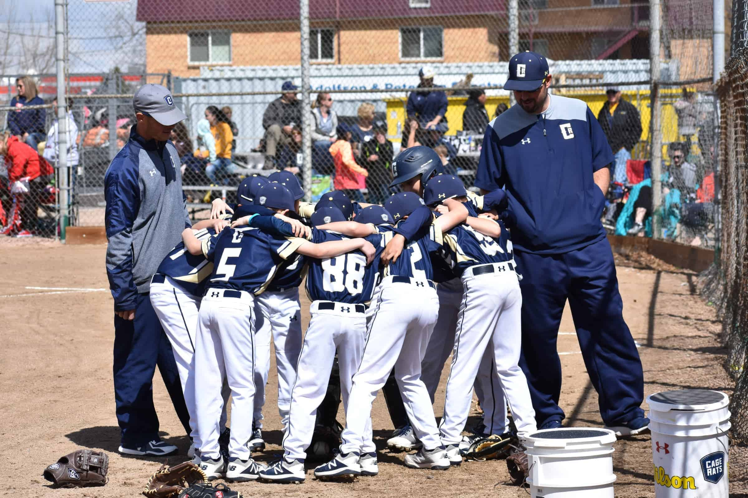 youth baseball coach huddling with team